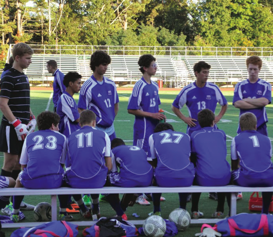 Junior Toma Beit-Arie (number 13) discusses strategy with the soccer team during a game against Weymouth on Sept. 26. Beit-Arie was recently named one of the captains for the 2014 season. He will be responsible for boosting team chemistry.
