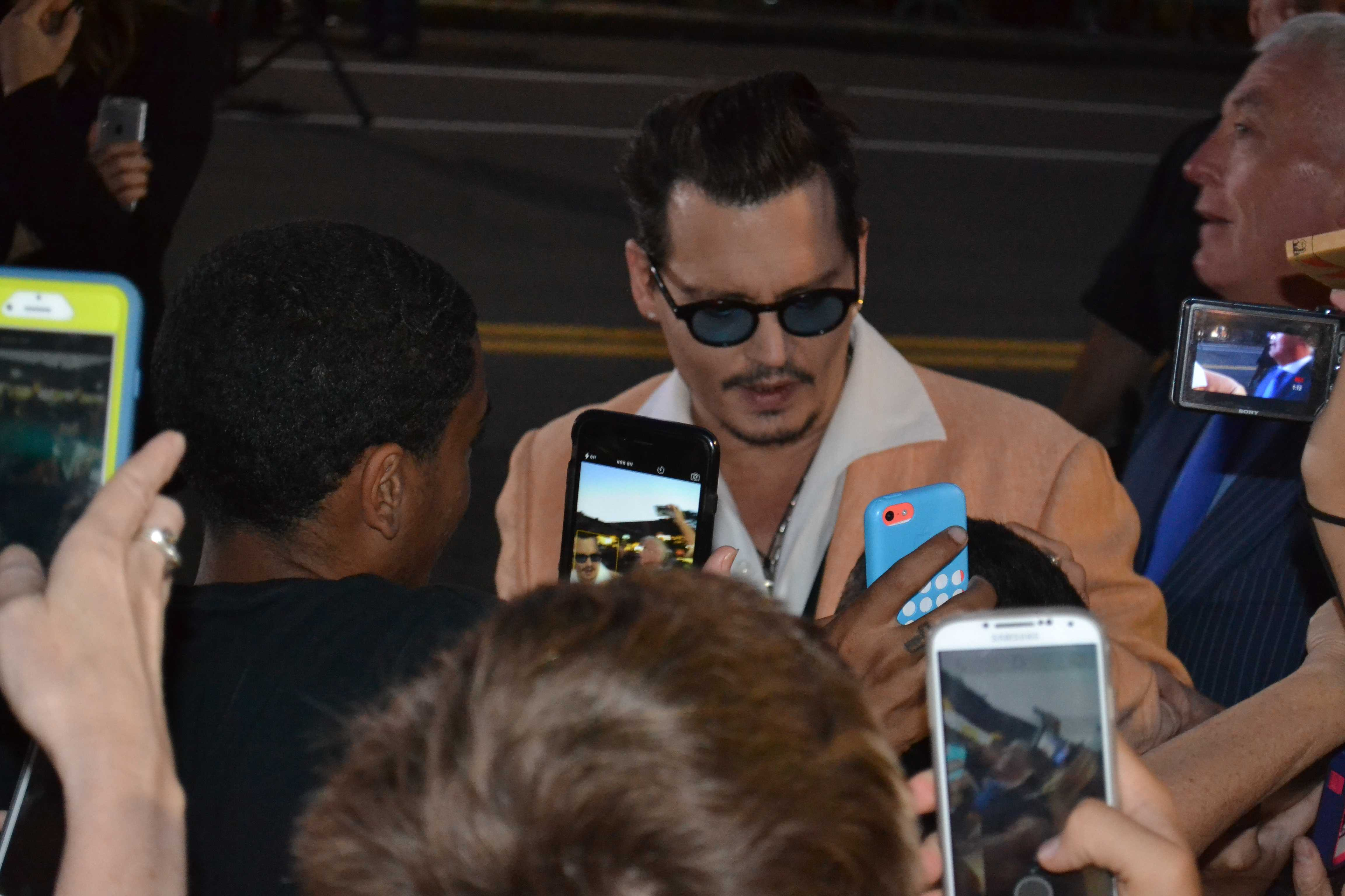 Actor Johnny Depp signs an autograph for a fan. Photo by Kendall McGowan.