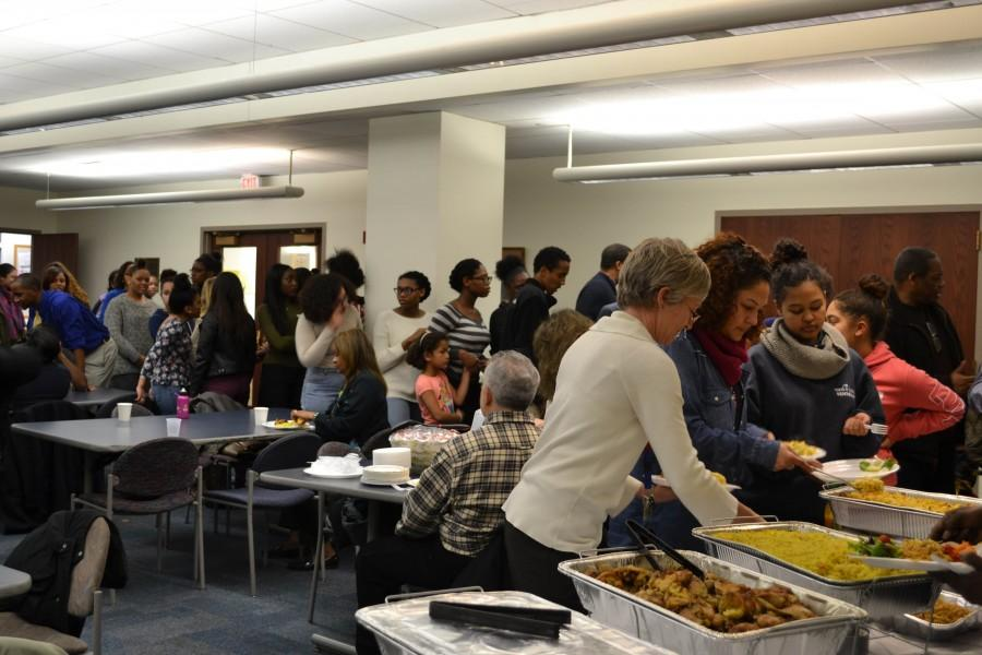 JACOB SPIEGEL/ SAGAMORE STAFF Students, parents and faculty alike stand in line to receive Kwanzaa dinner. Headmaster Holman helps herself to some Kwanzaa food.