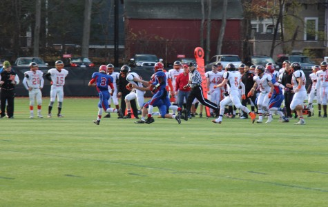 The boys football team battles Newton North on Nov. 26. The football team, along with other programs at the high school, hold its athletes to stricter grade policies than the ones instituted by the MIAA.