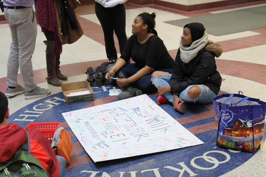 Seniors Donnaya Brown and Anijah Lender sit next to a petition poster in the atrium on Jan. 29. Leon Yang / Sagamore Staff