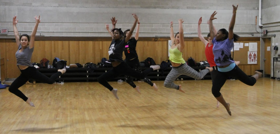 From left to right, juniors Noam Orem, Janel Mitchell, Lili Olsen and Keiantey Gamble perform stag jumpsacross the floor during class.