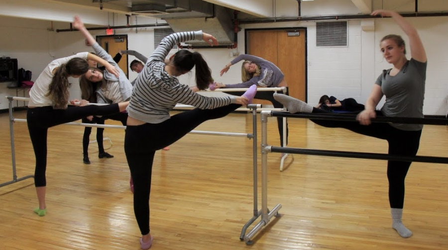 Dance teacher Kathleen Exar's E block intermediate class is in the midst of stretching for their day of ballet. The students use ballet bars towards the beginning of class to warm up, extending their legs onto the bar and stretching their splits. Below, Exar leads the students in continuous pirouettes across the floor to end class.