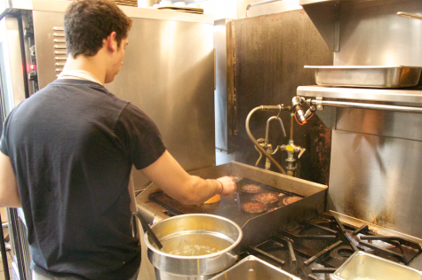 Sophomore Yuval Ore flips burgers in the Restaurant 108 kitchen. The course offers hands-on experiences and real career training.