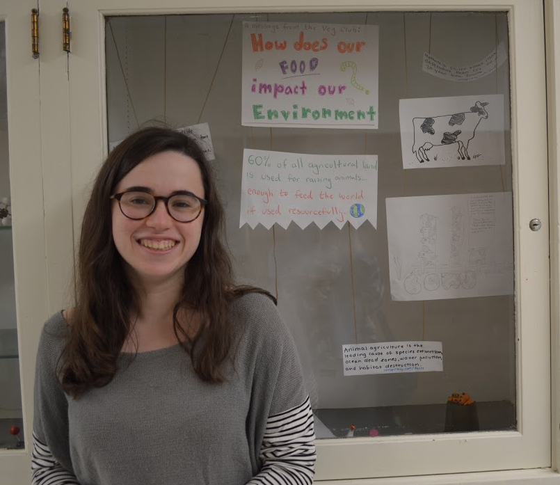 Junior Hannah Farman stands in front of the display case created by the high school's Vegetarian Club. The display case shows the environmental effects of eating meat. Sara Hogenboom / Sagamore Staff