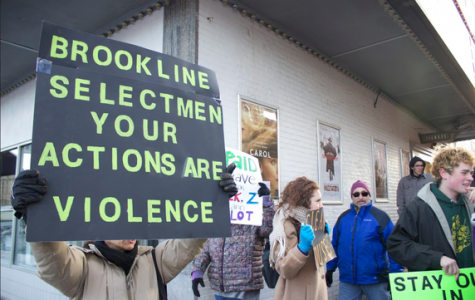 A woman holds a sign at the protest in front of the Coolidge Corner Theatre on Jan. 18. Protestors showed their support for Officers Prentice Pilot and Estefinos Zerai-Misgun.