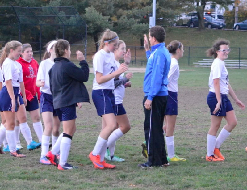 Freshmen girls soccer coach Dave Mitchell high-fives his team. Freshman athletes find that sports teams provide both social and academic advantages. Provided by Tyson Goldthwait.