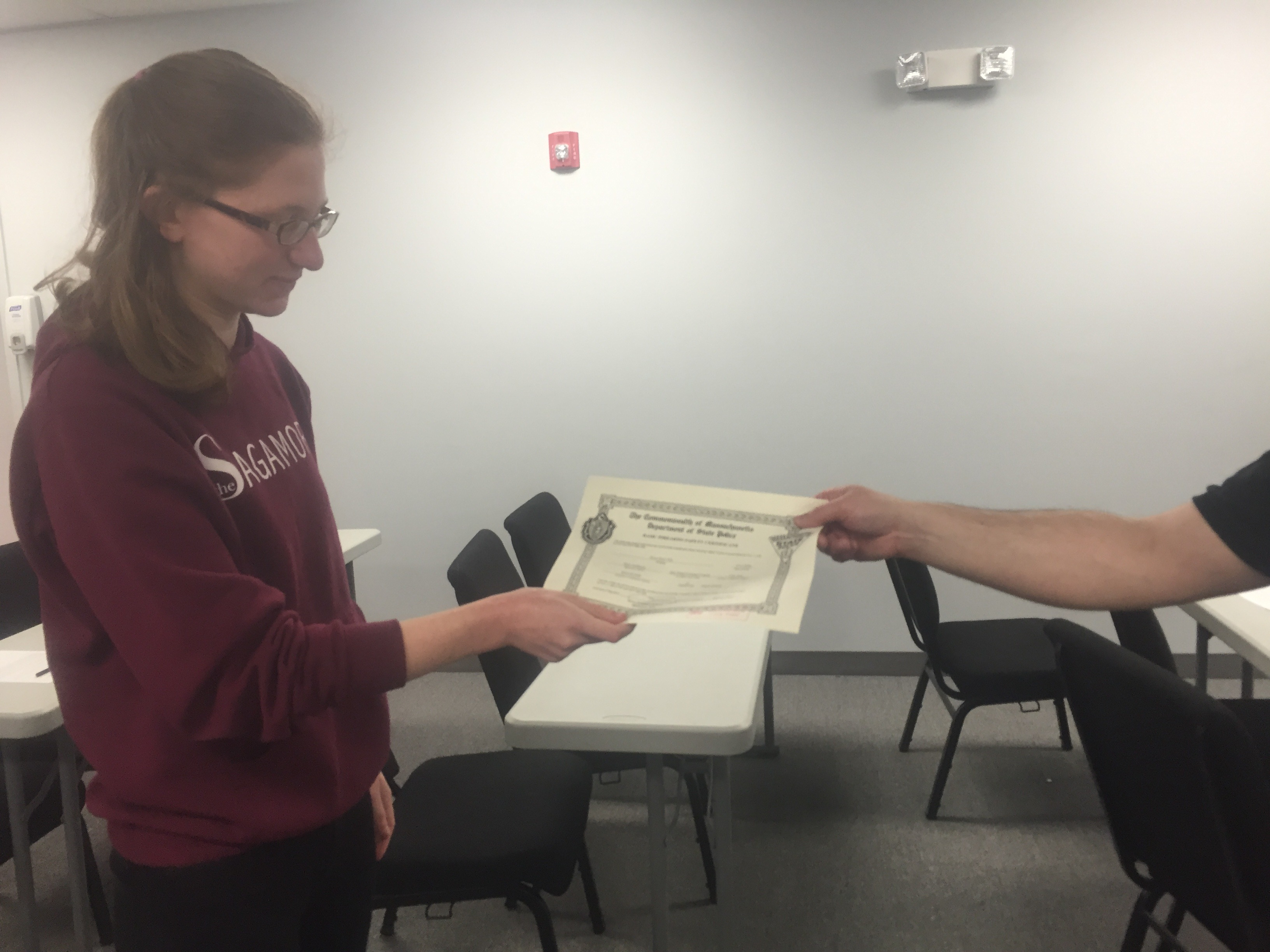 A Sagamore reporter receives her certificate from the instructor at the end of the Basic Firearms Safety Course.