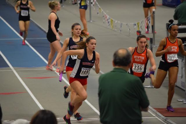 Sophomore Erin O'Brien hands the baton to her twin Katherine in the 4x400 relay. Twins participating on the same sports team face a mix of more intense competition as well as a unique support system.