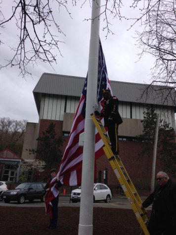 Elmon Hendrickson, Commander of the Brookline American Legion Post 11, raising the U.S. flag.