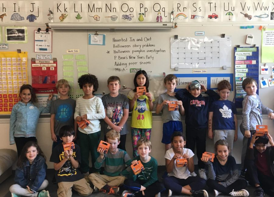 Second grade students at Heath show their UNICEF boxes filled with donations collected this Halloween. The club aspires to top last year's total amount of $200.