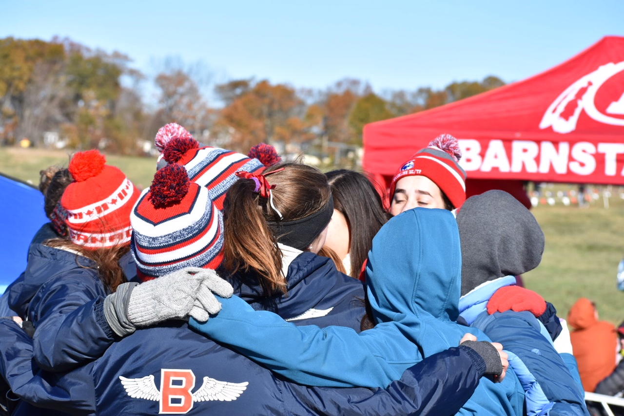 The girls cross country team celebrates together after placing 4th at the Eastern Massachusetts Divisional meet and qualifying for states, where they finished 17th.