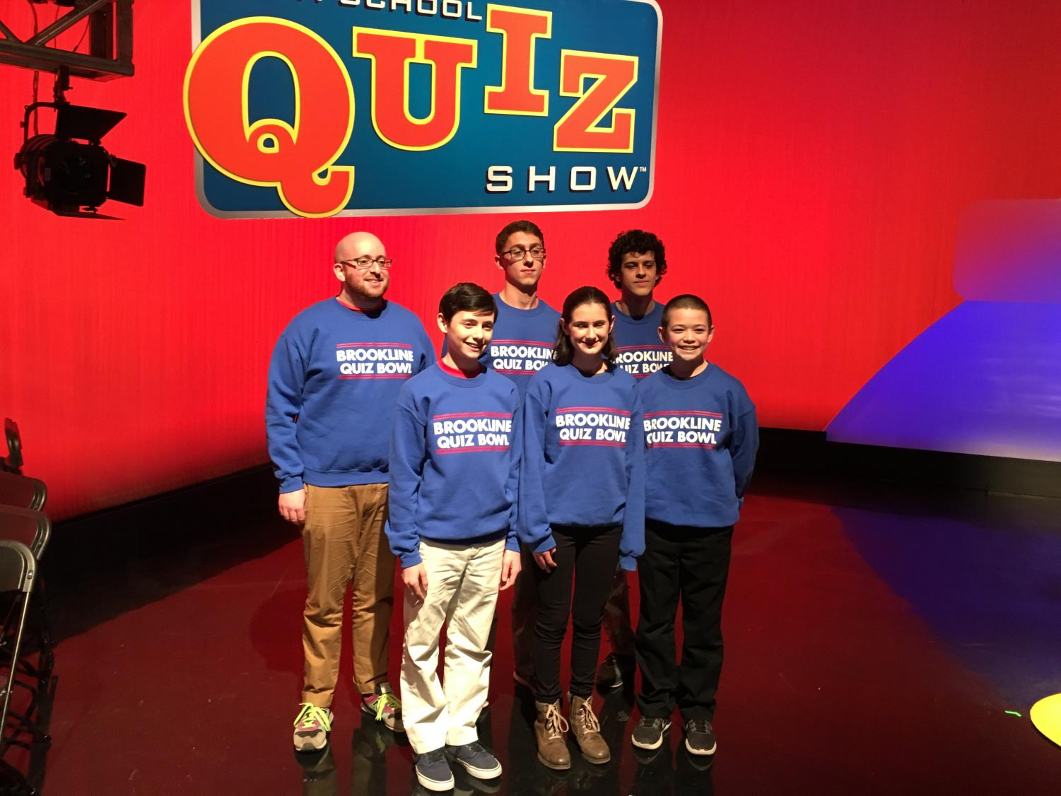 Five student competitors from the high school and teacher advisor Adam Fried pose on the set of the High School Quiz Show.