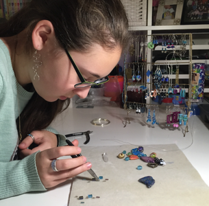 Maya Krantz 17' works intently on a piece of jewelry with a pair of pliers. Krantz took a metal working class at the high school, which has become an important part of her life.