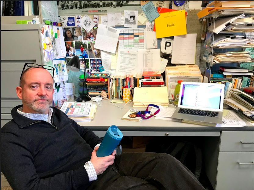 Primmer sits in front of his desk, which is jam-packed with books and other items he has collected over the years. His things showcase his passion for both literature and film, the key components of his classes at the high school.
