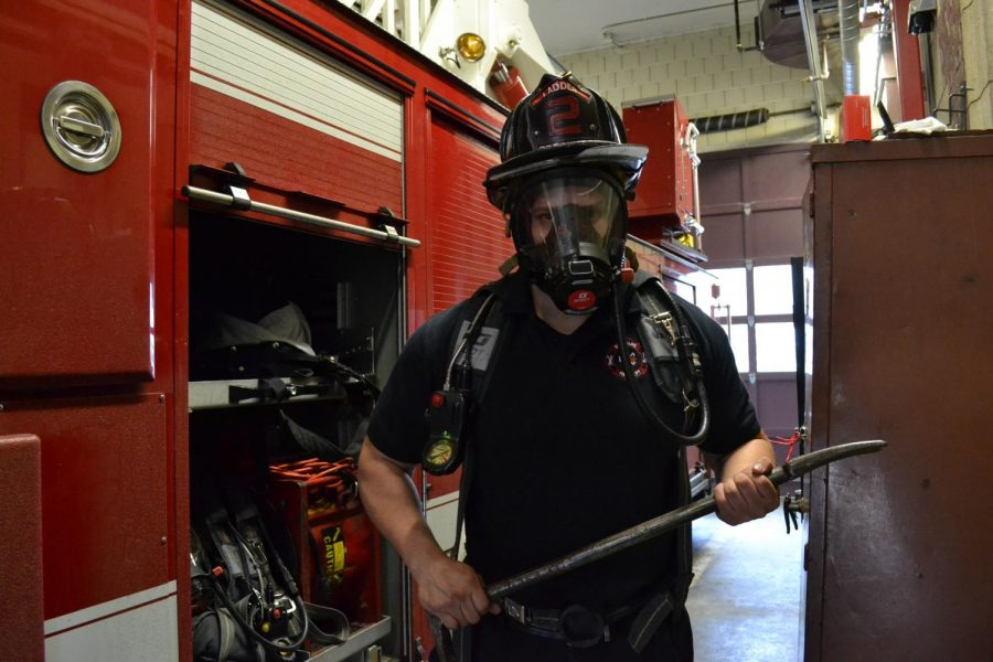 Firefighter David Luengas-Guayda demonstrates how essential pieces of fire equipment, like the oxygen tank and mask, function.