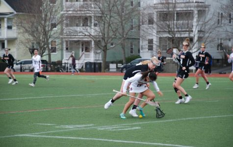 Lizzy Moy #19 going for a groundball in a game against Newton North.