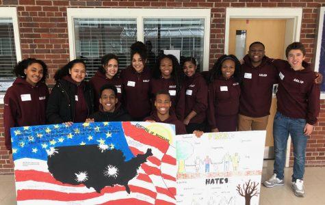 Students pose with murals they presented as part of the Tenacity Challenge. The four-part competition brought together students of color from local high schools.