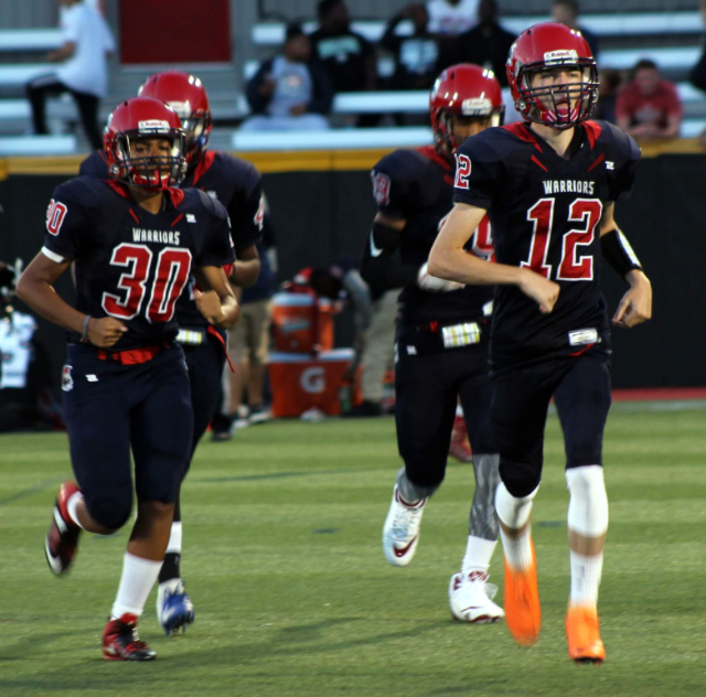 Senior Jordan Dias (left) runs on the field with her teammates. Under the Federal Title IX Law, Dias is able to participate on the traditionally all-boys football team.