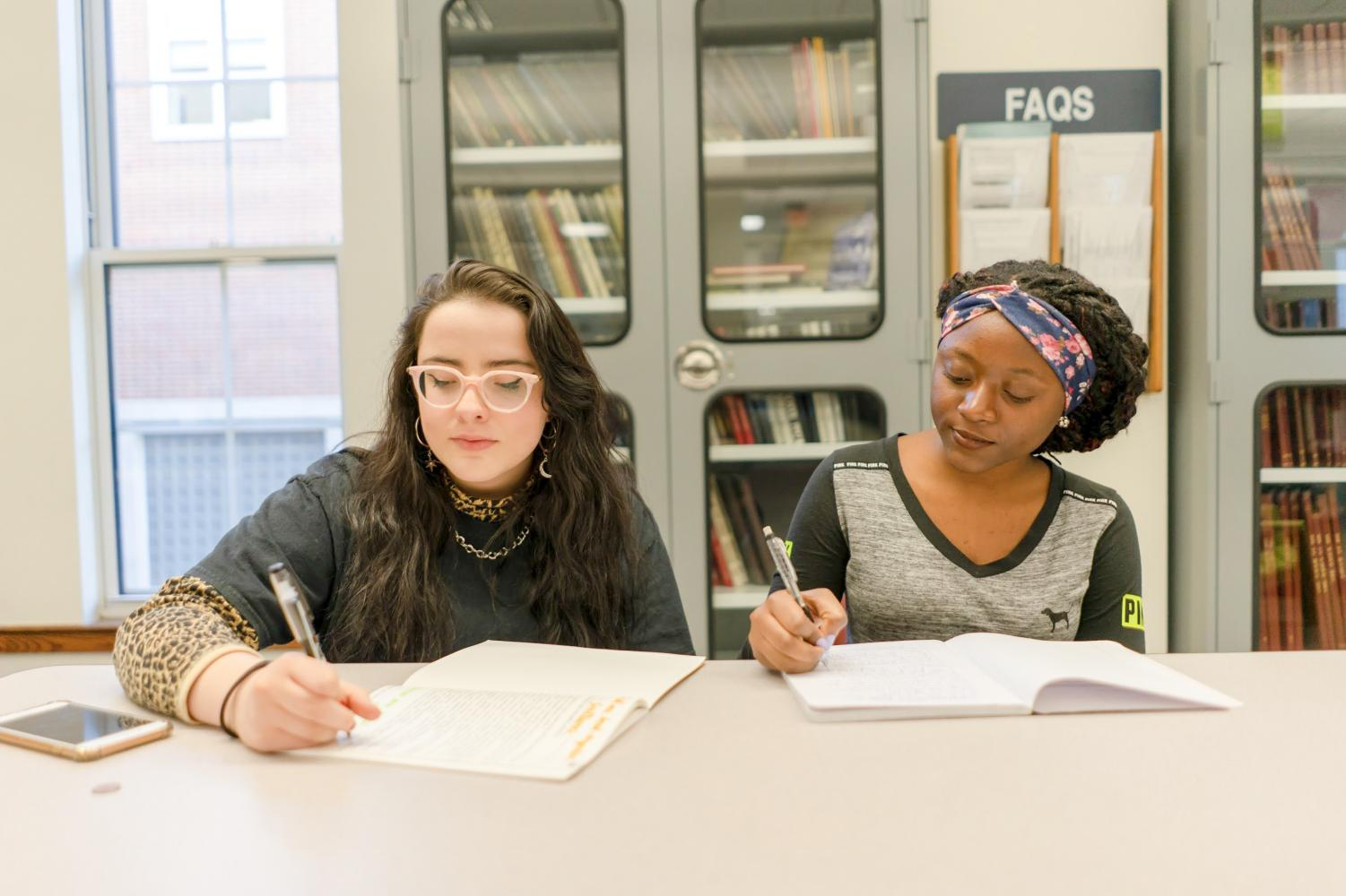 Seniors Isabella Moros Camargo and Konah Brownell diligently complete school work.  Both have concerns about applying to college as an immigrant.