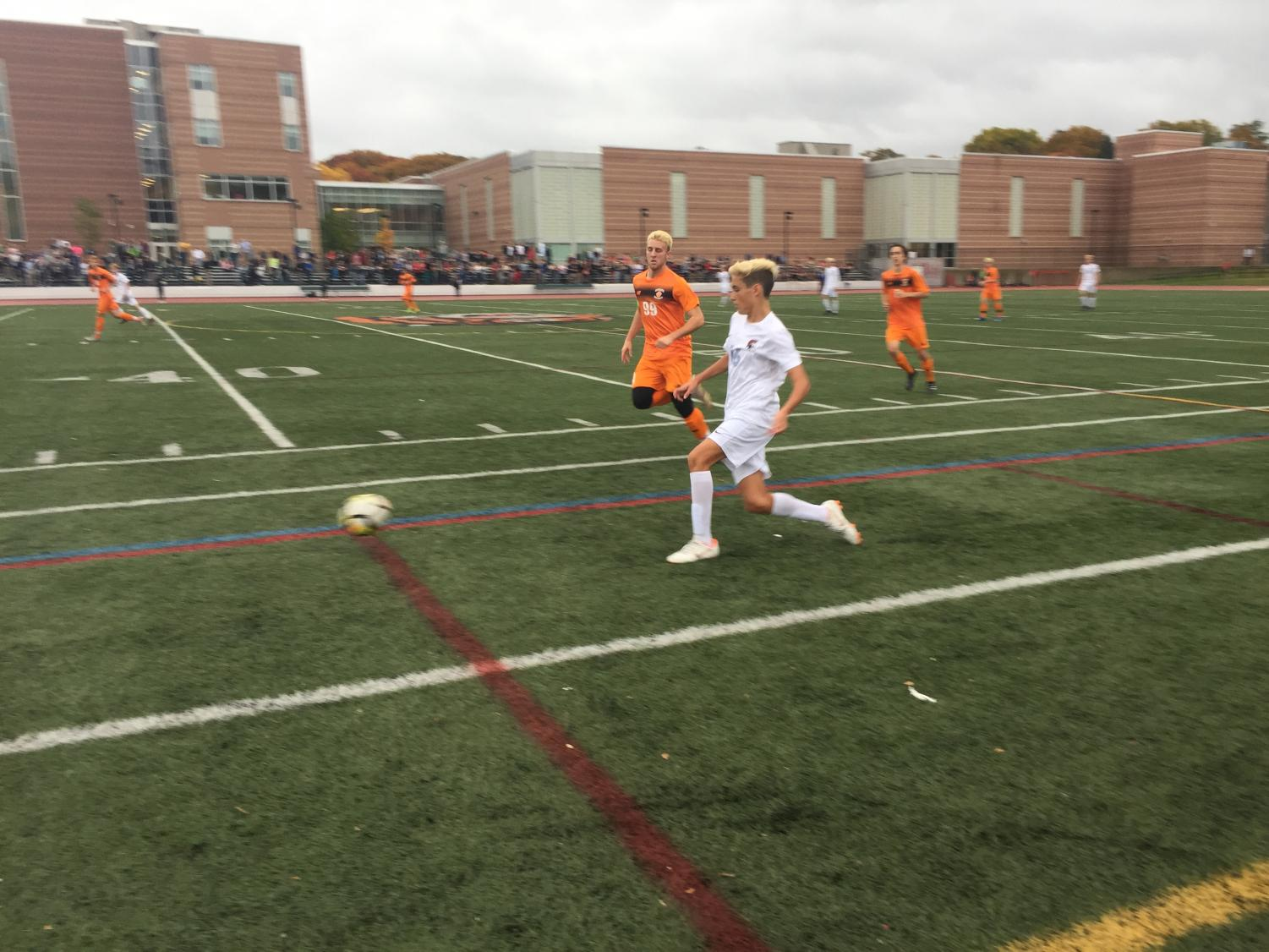 Junior Manuel Lancastre takes the ball up the field in a playoff game versus Newton North. Coach Kyle-Beaulieu-Jones attributes the team's success this season to their bond.