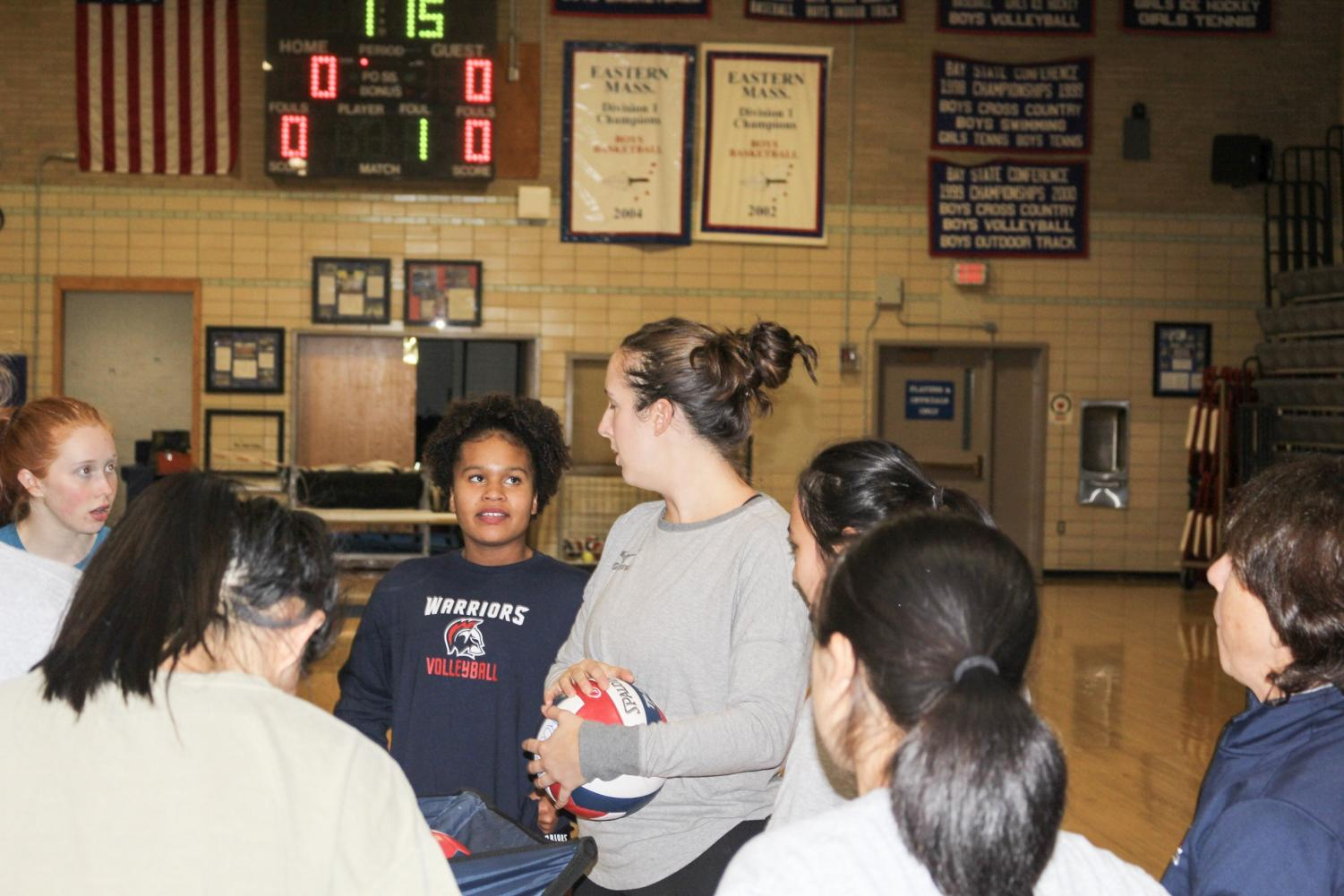 Girls varsity volleyball coach Erin Deenen talks with her team after practice. Her approach to coaching teaches her players skills that will translate into the real world.