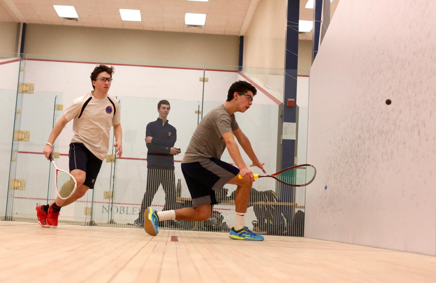 Senior Josh Fleishman (right) strikes the ball on the back wall of the court during a squash match. Squash players feel that having a tennis background helps them with the sport.