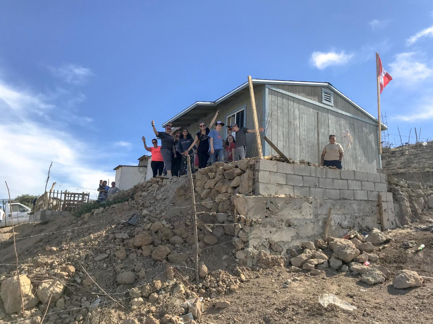 Mallik and her entire team stand and wave joyfully in front of the completed house on the final day of their trip in Enseñada, Mexico