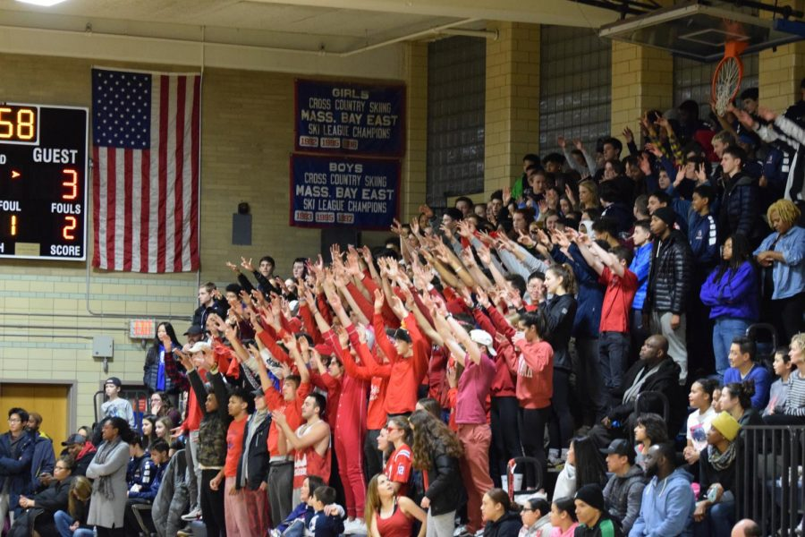 The crowd of students and family members cheer on the team during a boys varsity basketball game.