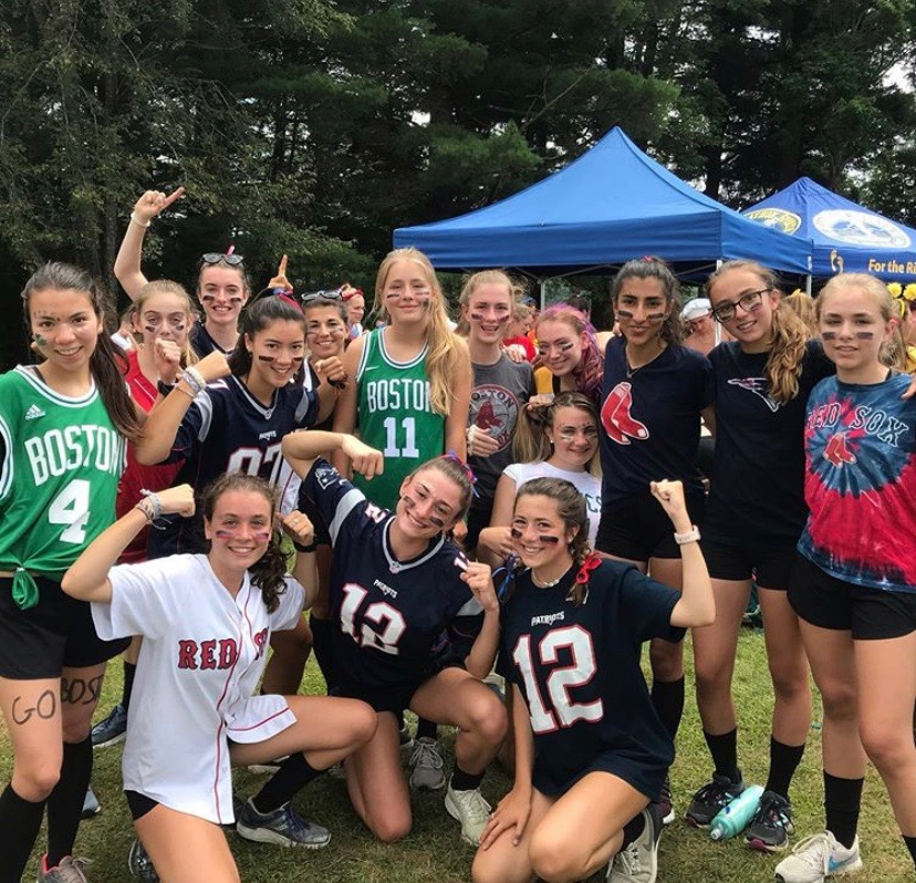 Members of the girls cross country team wearing Boston sports team spirit pose during their camp competition. The camp provides a key bonding experience.
