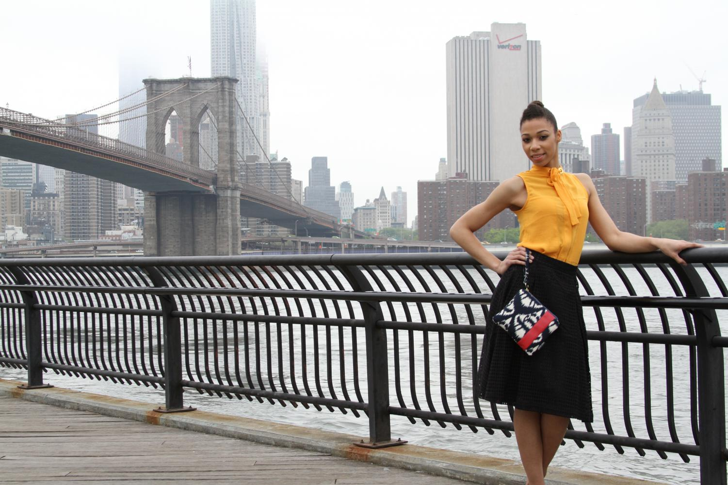 Janeica Hance poses with her original handbag near the Brooklyn Bridge in NYC. The Brookline alum works in management and runs her own business called J. Hance where she designs clutches.