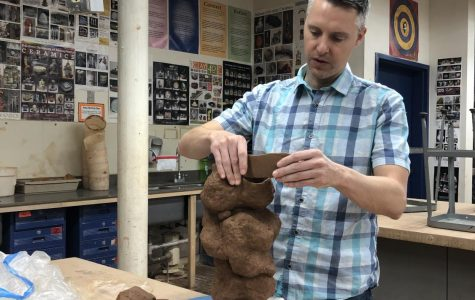 Ceramics teacher Andrew Maglathlin works on a clay sculpture in the ceramics studio, which is potentially at risk from dust.