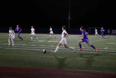 Junior Max Luby speeds past a defender from Newton South. The Warriors were down most of the game 1-0, but scored the equalizing goal in the 76th minute and ended the game with a tie.